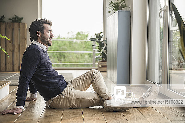 Junger Mann sitzt auf dem Boden  schaut aus dem Fenster und entspannt