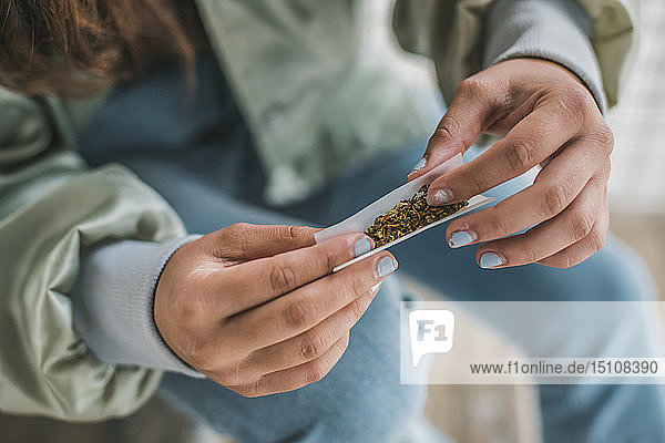 Hände einer Frau beim Rollen eines Marihuana-Gelenkes  Nahaufnahme