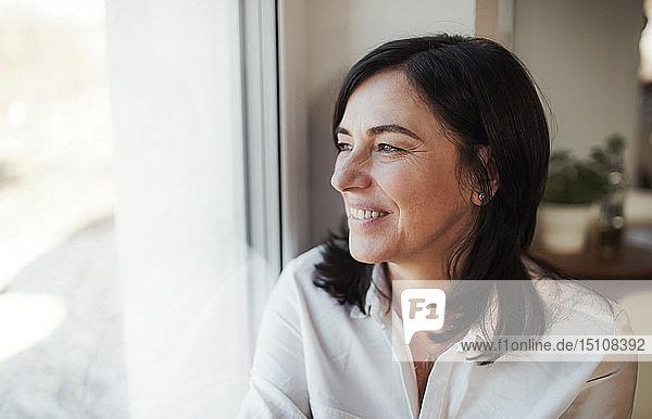 Reife Frau schaut aus dem Fenster