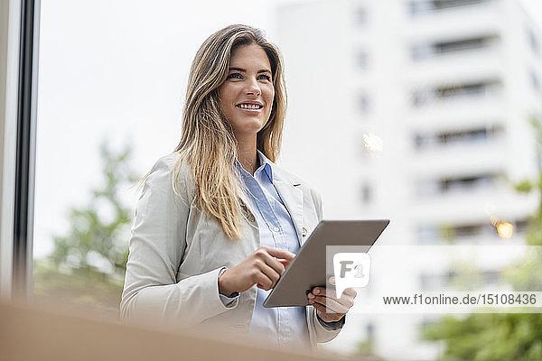 Porträt einer jungen Geschäftsfrau mit Tablett  im Hintergrund Bürogebäude
