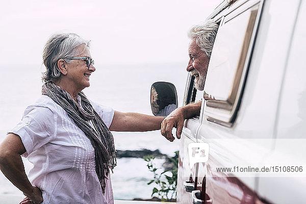 Älteres Ehepaar reist in einem Oldtimer-Van  macht eine Pause am Meer  unterhält