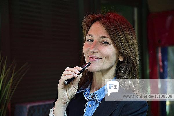 Porträt einer reifen Frau  die eine elektronische Zigarette raucht