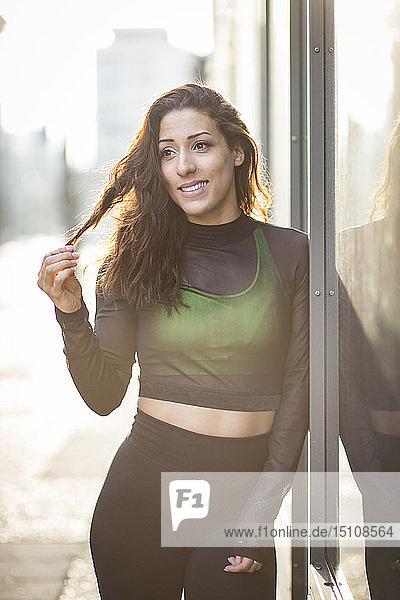 Porträt einer lächelnden  sportlichen jungen Frau in der Stadt