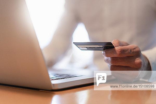 Männerhände  die eine Kreditkarte halten und während einer Online-Zahlung mit einem Laptop  Nahaufnahme