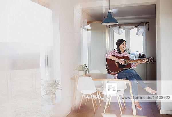 Reife Frau spielt zu Hause Gitarre