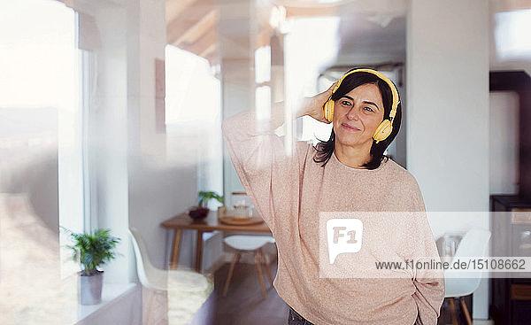 Reife Frau hört Musik mit gelben Hardphones