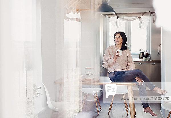 Reife Frau sitzt am Küchentisch und trinkt Kaffee