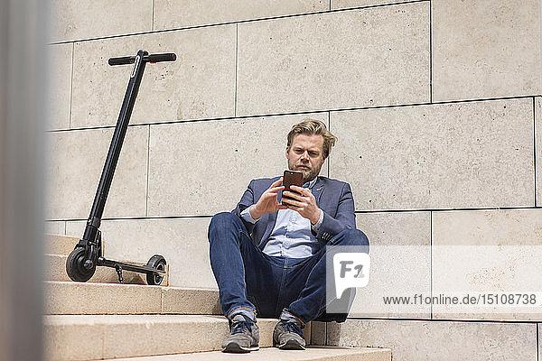 Geschäftsmann mit E-Scooter sitzt mit Smartphone auf der Treppe