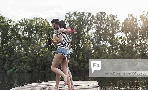 Happy young couple having a drink and embracing on jetty at a remote lake