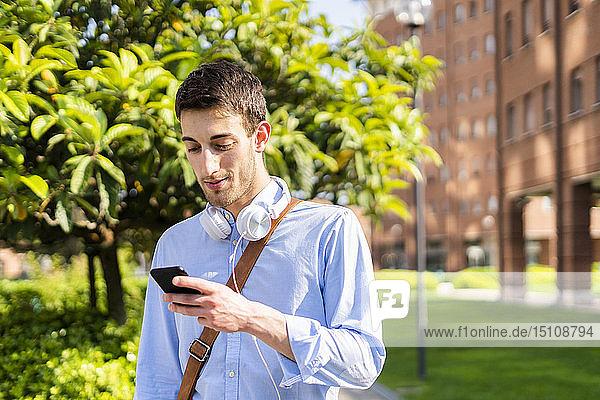 Junger Mann benutzt Smartphone  Kopfhörer um den Hals