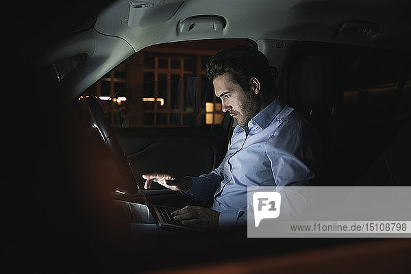 Young man using laptop in car at night