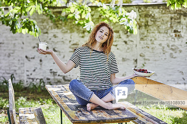Portrait of young woman sitting on wooden table in garden holding bowl of berries and glass of yoghurt