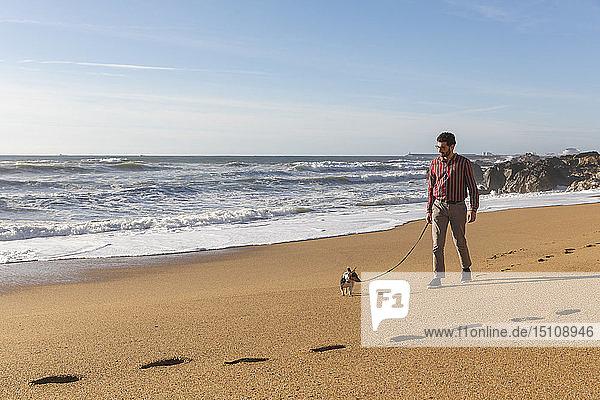 Portugal  Porto  junger Mann  der mit seinem Hund am Strand spazieren geht