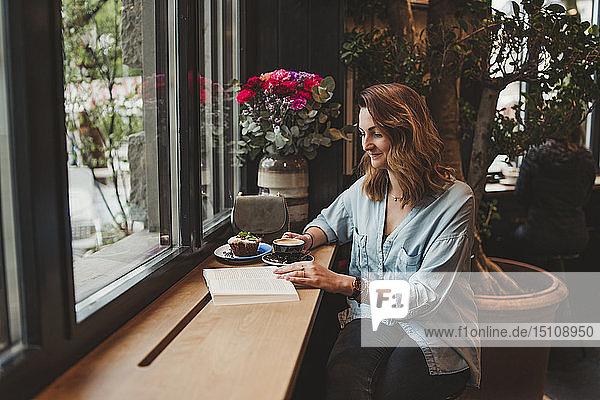 Junge Frau liest ein Buch in einem Cafe