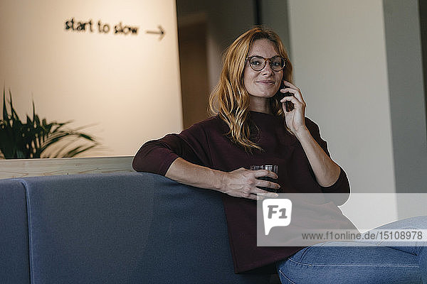 Lächelnde junge Frau sitzt auf der Couch und telefoniert mit dem Handy