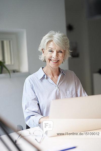 Porträt einer lächelnden reifen Frau mit Laptop am Schreibtisch