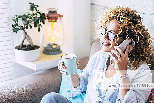 Woman on couch at home with coffee mug on cell phone