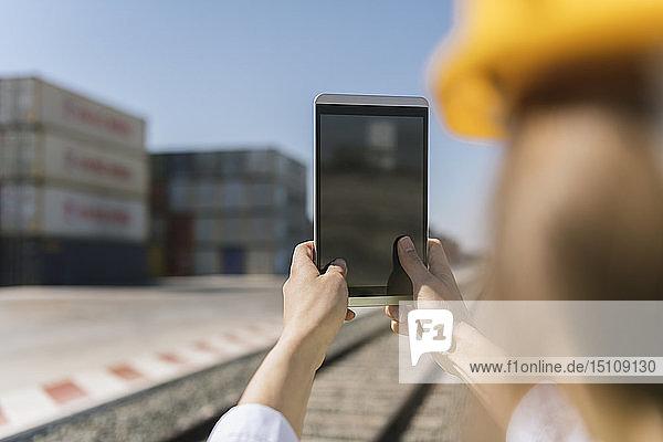 Nahaufnahme einer Arbeitnehmerin  die eine Tablette auf der Eisenbahn in der Nähe von Frachtcontainern auf einem Industriegelände in der Hand hält