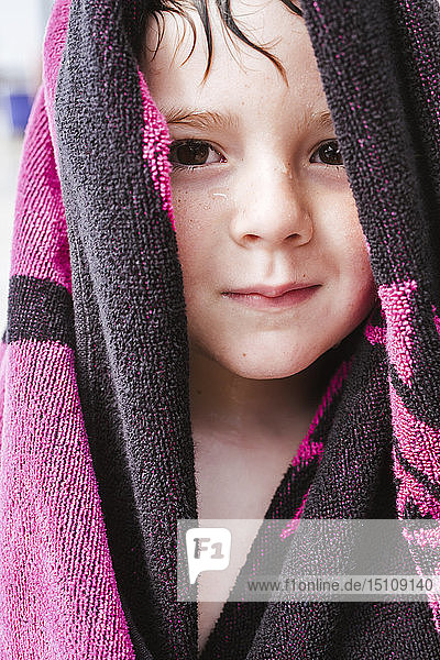 Portrait of wet little boy with towel on his head