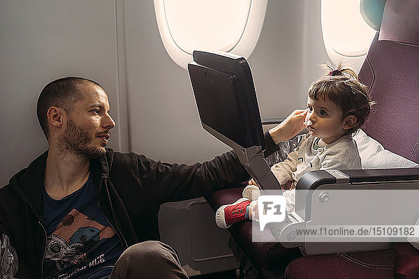 Little girl watching movie on screen during a flight while her father taking care