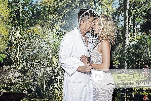 Young couple standing in front of photo wallpaper  kissing behind tennis racket