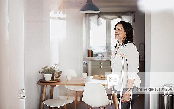 Reife Frau mit Krücken  allein zu Hause