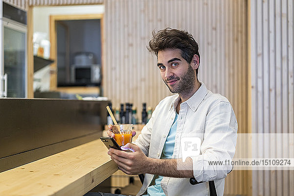 Portrait of a man with cell phone sitting at the counter of a bar having a drink
