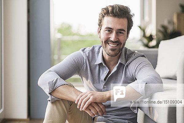Porträt eines jungen Mannes  der in seinem Wohnzimmer sitzt