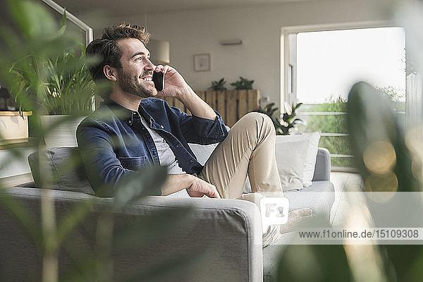 Junger Mann sitzt zu Hause auf dem Sofa und benutzt ein Smartphone