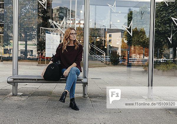 Junge Frau sitzt mit Tasche an Bushaltestelle