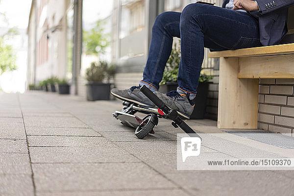 Geschäftsmann mit gefaltetem E-Scooter auf dem Bürgersteig  Teilansicht