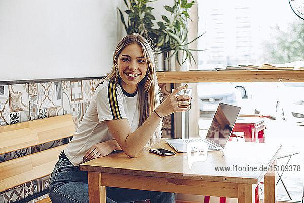 Junge Frau benutzt das Mobiltelefon und den Laptop im Café