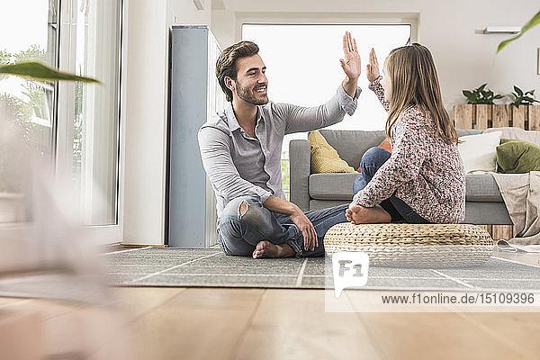 Junger Mann und kleines Mädchen sitzen zu Hause und geben High Five