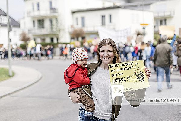 Mädchen mit Baby auf dem Arm hält ein Plakat auf einer Demonstration für Umweltschutz