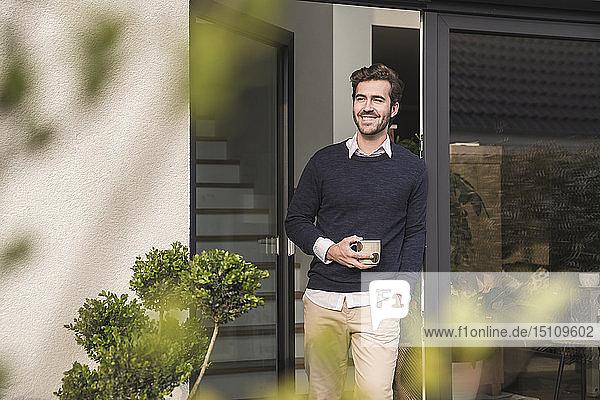 Junger Mann lehnt in der Tür seines Hauses  mit einer Tasse Kaffee