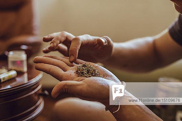 Nahaufnahme einer Hand  die einen Joint Marihuana vorbereitet