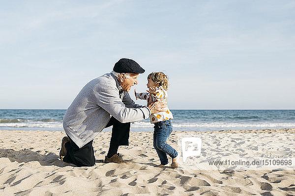 Großvater spielt mit seiner Enkelin am Strand