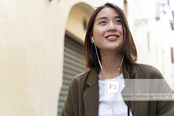 Italy  Florence  young woman with earphones phone in the city