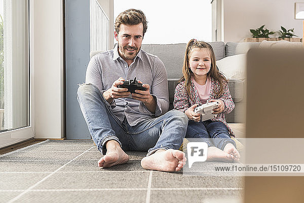 Junger Mann und kleines Mädchen spielen Computerspiel mit Spielkonsole