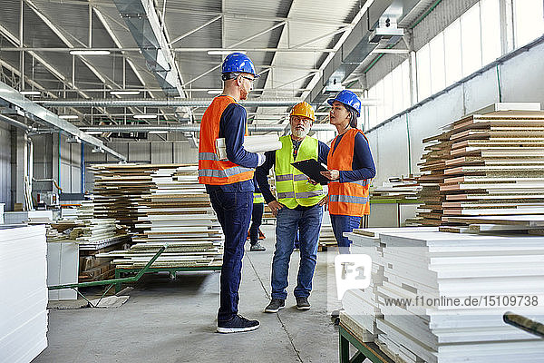 Kollegen in Arbeitsschutzkleidung im Gespräch in der Fabrik