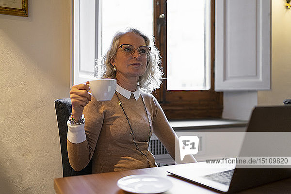 Portrait of mature businesswoman sitting at table with laptop drinking cup of coffee