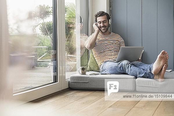 Junger Mann sitzt auf einer Matratze  benutzt Laptop mit Kopfhörern
