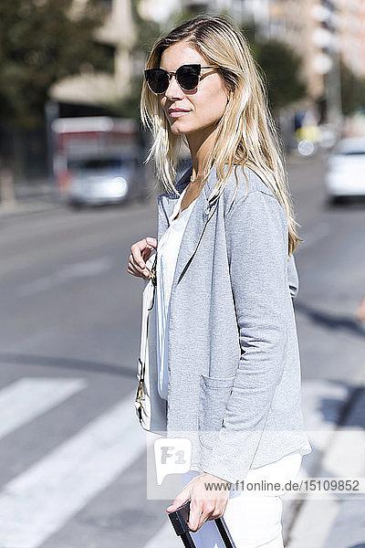 Junge Geschäftsfrau schaut seitwärts  während sie mit der Reisetasche die Straße überquert