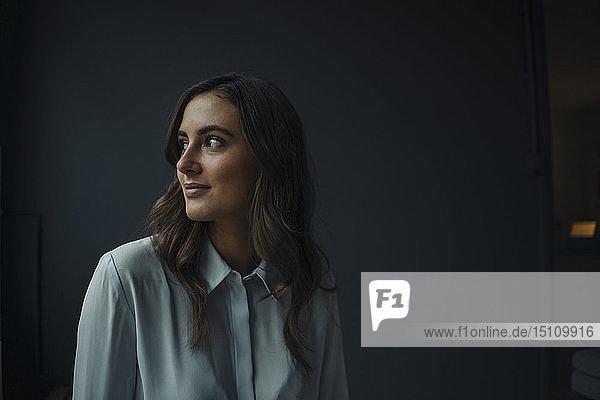 Porträt einer lächelnden jungen Geschäftsfrau  die zur Seite schaut