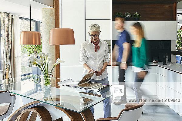Ältere Frau steht im Ausstellungsraum eines Möbelhauses und schaut auf den Katalog
