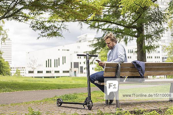 Geschäftsmann mit E-Scooter sitzt auf einer Bank im Stadtpark und benutzt ein Smartphone  Essen  Deutschland