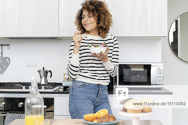 Woman eating strawberries at home