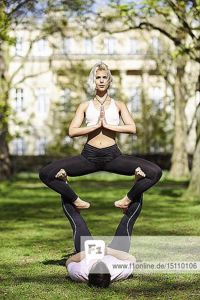 Junges Paar macht Yoga-Akrobatik in einem städtischen Park