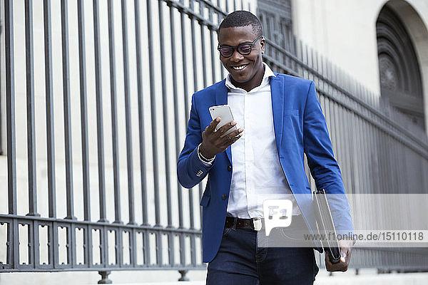 Junger Geschäftsmann in blauer Anzugsjacke und mit Smartphone