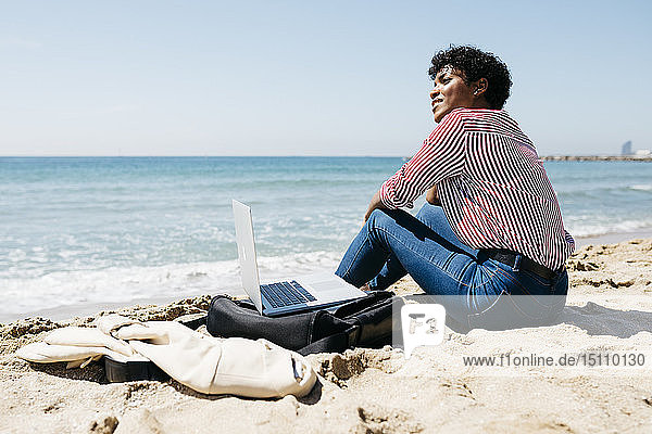 Woman sitting on the beach while working with the laptop
